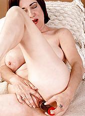 Wild MILF enjoys her black dildo in bed
