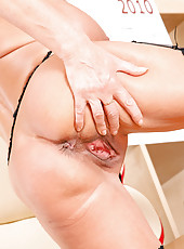 Naked mature babe Elaine shows off her shaved Anilos pussy on top of her office table