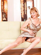Lovely milf hottie Elaine bares off her body and gently tickles her perky mature pussy on the sofa