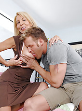 Blonde haired milf sucks a huge cock and gets fucked in bed by a stud with a huge load of cum