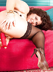 Mature Anilos cougar Gilly stuffs her mature pussy with the rabbit on the couch