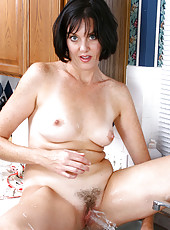 Totally nude housewife shows off her milf breasts and her dripping pussy in the kitchen