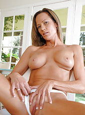 Sensual cougar Montana Skye lovingly torments her bald mature pussy with the purple rabbit