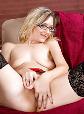 Horny mature stunner spreads her shaved Anilos pussy on the sofa after getting home from work