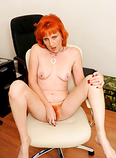 Hot redheaded cougar satisfies herself with a dildo while doing her daily tasks in the office