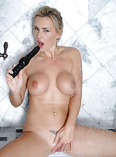 Alluring mature babe Tanya Tate gently strokes her pussy with the rabbit toy while showering