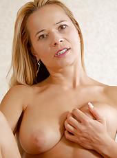 Busty Anilos Viktoria caresses her clitoris on top of her desk