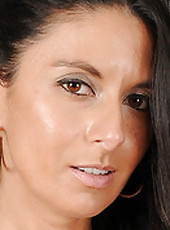 Elegant MILF Nikki Daniels strips naked and plays with her big clit