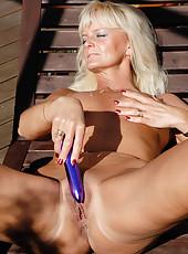 43 year old blonde Jenny F slips her long purple dildo deep inside