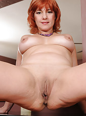 Redheaded 52 year old MILF Calliste strips off her elegant dress for you