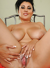 Brunette MILF with massive juggs strips and spreads her pussy