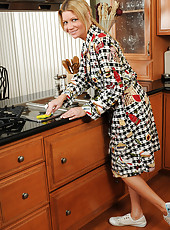 Beautiful blonde MILF Christina strips and bares all in the kitchen