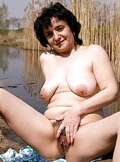 Sandra tugs at her full bush while enjoying the scenes at the waterfront