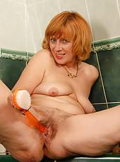 59 year old Karoline scrubbing her hairy bush in the bath