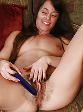 Spicey MILF with a very hairy pussy toys herself for the camera