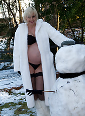 Pregnant and mature Jan warms up after playing outside in the snow