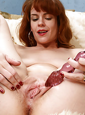 Redheaded MILF Megan slips a large dildo into her 30 year old pussy