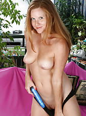 Redheaded mature chick stuffs a blue dildo up her shaved pussy