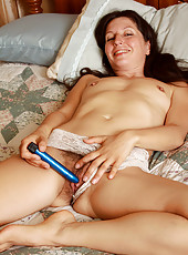 Toying 41 year old Carmen T slides a blue vibrator deep inside her