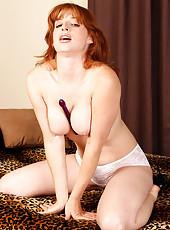 Playful and redheaded MILF Amber D slips a dildo deep inside