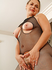 Serenity in a fishnet bodysuit spreads her mature ass and pussy