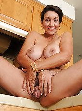 Busty MILF Persia takes a break to tug at her hairy 53 year old pussy