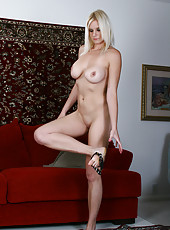 Busty blonde MILF Slovanna toys her meaty pussy on the couch