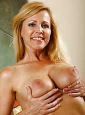 Blonde and busty Nicole strips out of her long dress and poses