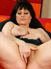 Big titted brunette MILF fingers her mature pussy on the bed