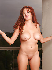 Busty redheaded MILF spreads wide on the balcony