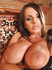 Busty latex babe fingering her twat
