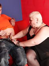 Shorthaired mature fatty sucks a boy stiff and rides him