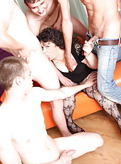 Oldie's hairy pussy takes a pounding from a crowd of guys