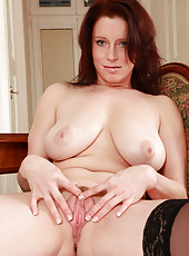 Busty and elegant redheaded MILF Carol swings her massive bangers