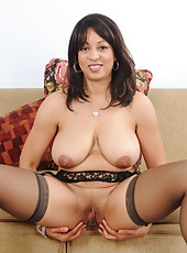Busty Lala Bond shows off her garder and stockings in the livingroom