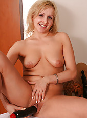Blonde mom fills her mature box with a big black dildo in here