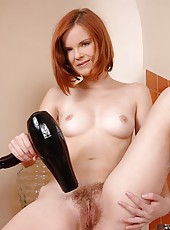 Saucy redhead plays with her pussy