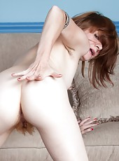 Looking at Zia, the American redhead, brings out the best of a redhead. She slowly strips near the couch and shows off her sexy figure which has hairy pits, a furry hairy pussy, and a sexy figure.