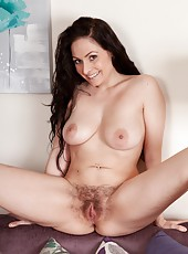 Sophia Delane begins to take off her clothes eager to show off her mound. Bending over the couch she gives the perfect view of her hairy bush, as she plays with her pussy for the camera.