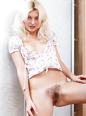 Fedora is a sexy blonde that sits down on a red couch and slowly and seductively strips out of her skimpy outfit until she is naked and then she spreads her legs apart and shows her hairy pussy.