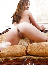 Hairy woman Era is sitting on her yellow couch in the living room as she slowly strips out of her tank top and her panties and then she spreads her legs far apart and shows off her hairy pussy.