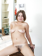 Emilia is so pretty in her nice pink dress, but she has other things in mind. She loves to take off her clothes and expose her very hairy pussy, but she doesn