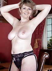 Sophie UK enjoys dressing in an evening gown with a pair of stockings and garter belt, especially if her fans are watching.  She takes out her large natural tits and fingering her hairy pussy.