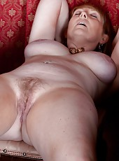 Strawberry blonde milf, Sophie UK loves to get out of her long dress, to show off her large natural breasts and her hairy pussy.  She strips next to her piano and runs her fingers in her hair.