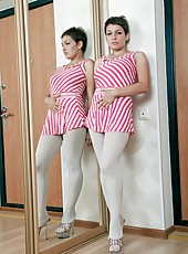 Standing in the corner of her bedroom next to her mirror, Karina likes to look at herself. She feels really sexy in her red striped dress, but she feels even sexier looking at her naked hairy pussy!