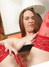Erin Eden bends her curvy natural ass over in red stocking and lingerie. Her dark thick pussy hair bursts out from all sides as she begins her slow seductive strip