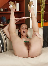 Kinky Erin Eden lfts her skirt, spreads her natural thighs and drives her dildo deep into her cum filled hairy pussy on the couch.