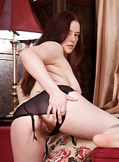 Ely Louise is hiding her favorite sexy black lingerie and stockings under her clothes. When she lays back on the sofa she cant wait to tease her meaty bush.