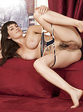 Turned on by her book, Angelina tears off her tight jeans, arches her back and rubs her fluffy pussy on the couch.