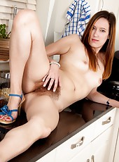 Hairy vixen Sadie Matthews finishes cleaning the kitchen and wants to relax. What better way then to strips off in the kitchen and finger her perfect hairy minge.